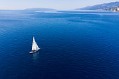 Opatija, Croatia, July 20, 2019: A man sails with a classic Dragon sailboat in front of Volosko Village