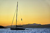 Sailing yacht in front of an island at dusk