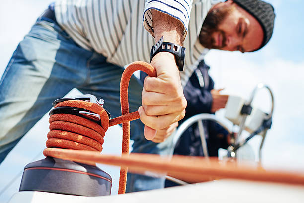 Sailing Concentrated seaman using rope to control movable corner of a sail sailor suit stock pictures, royalty-free photos & images