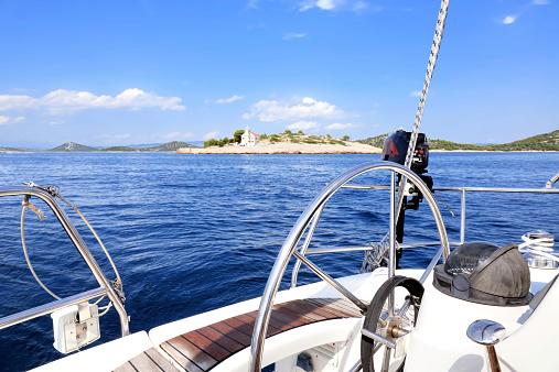 Sailing along Prisnjak lighthouse, Adriatic sea, Croatia.