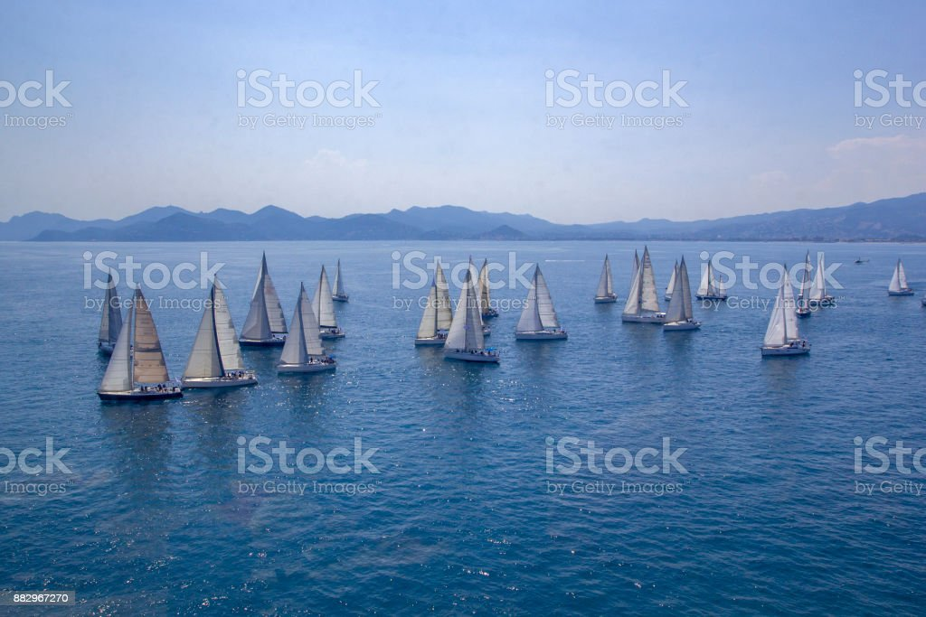 Sailing regatta or a group of small water racing boats in the Mediterranean, a panoramic view with blue mountains on a horizon stock photo