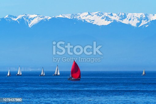 Sailing regatta with view of Olympic Mountain in the afternoon, British Columbia