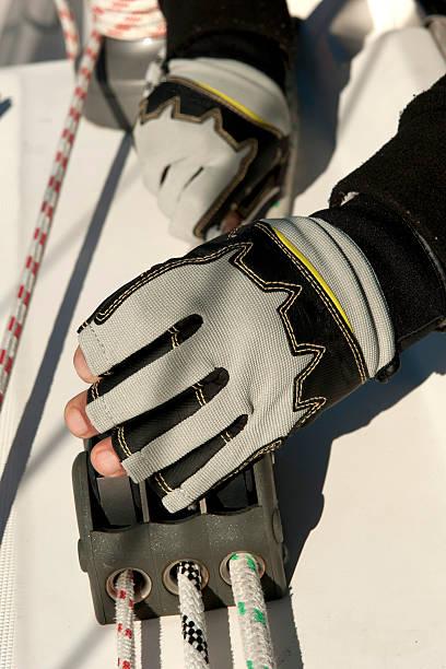 sailing rope clutch with sailor hand - segelhandschuhe stock-fotos und bilder