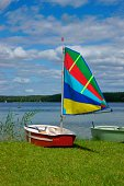 Sailing, sailboat Optimist with colored sail, stretched out on the shore of the lake