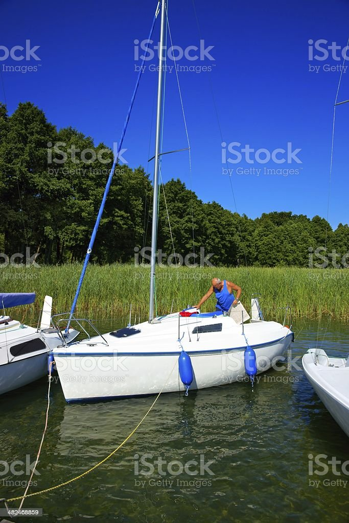 Sailing. Senior man preparing sailboat to depart from the marina. stock photo