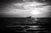 A silhouette of an old sailing ship during a sunset.
