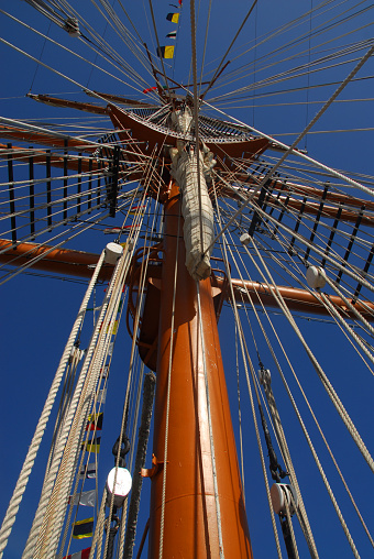 Lookin up a mast, sail yards, top, jacob's ladders, shrouds and rigging of a sailing ship against blue sky.