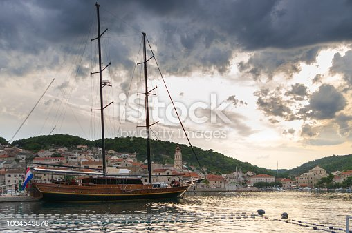 sailing ship moored in a small harbor in the small town of Pucisca on the island of Brac, in the background stone town buildings and a cloudy sky. Summer landscape before the storm. Summer travel destination.