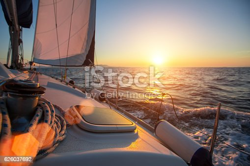 Sailing ship luxury yacht boat in the Sea during amazing sunset.