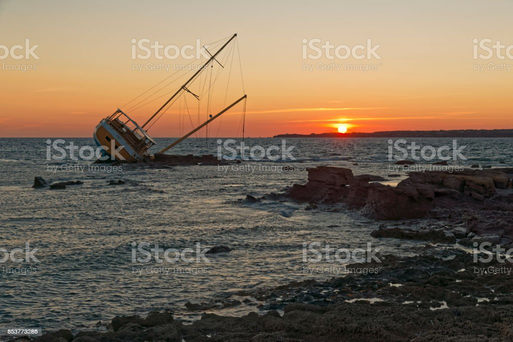Sailing ship stranded on the rocks stock photo