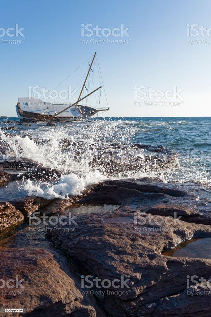 Sailing ship stranded on the rocks stock photo