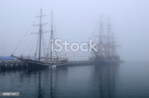 A foggy dawn slowly lifts to reveal tall ships in Greenport Harbor, New York