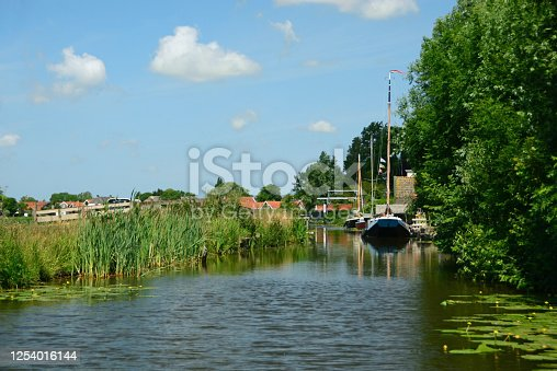 Fryske marren: Friesland  idyllic aerial view with small canal,sailing boat and roof tops.