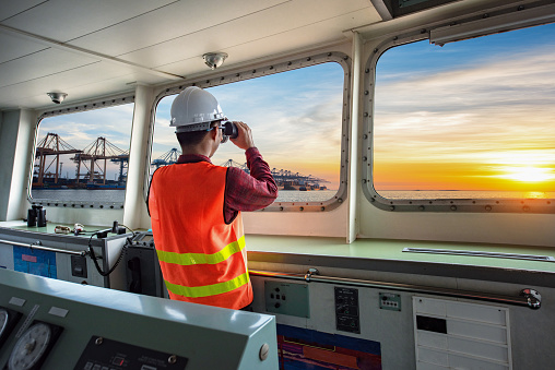pilot, port control or duty officer in charge handle of the ship navigating to the port destination, keep watching navigation on the bridge of the ship vessel under voyage sailing to the sea