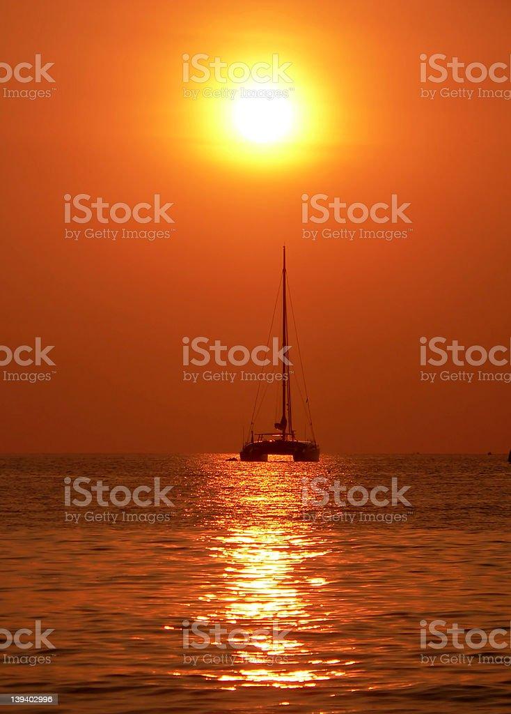 sailing towards hazy sunset royalty-free stock photo