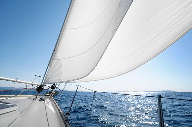 segeln auf den horizont an einem sonnigen tag - segeln stock-fotos und bilder