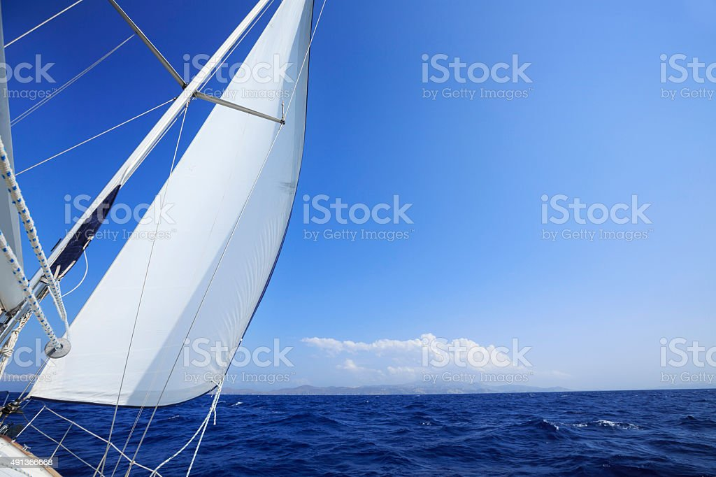 Sailing    White sails of sailboat  Beautiful blue sea in background stock photo