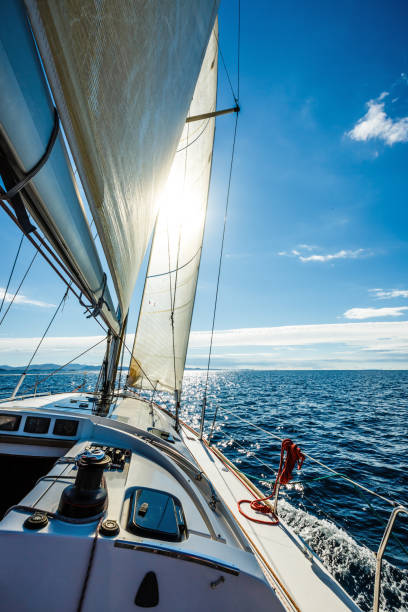 Sailing with sailboat towards the sun stock photo