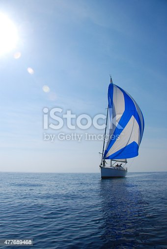 1011210354 istock photo Sailing with white and blue spinnaker 477689468