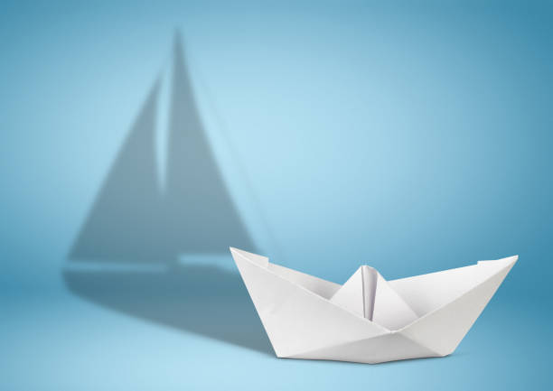 Sailing yacht concept, paper ship with sailing boat shadow on blue stock photo
