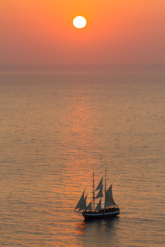 SANTORINI, GREECE - 2013 august. Sailing yacht In The Sunset At Santorini.