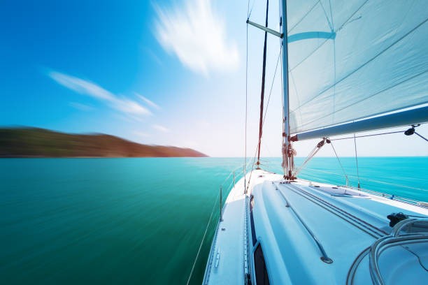 Sailing yacht moves in the sea under the main sail. Image is mottion blurred stock photo