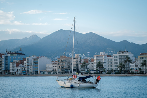 Sailing yacht, sailboat in the bay on city landscape and summer cloudy blue sky background. The boat is anchored in the bay with a calm sea. View from the sea to the coastal city. Roses, Catalonia.
