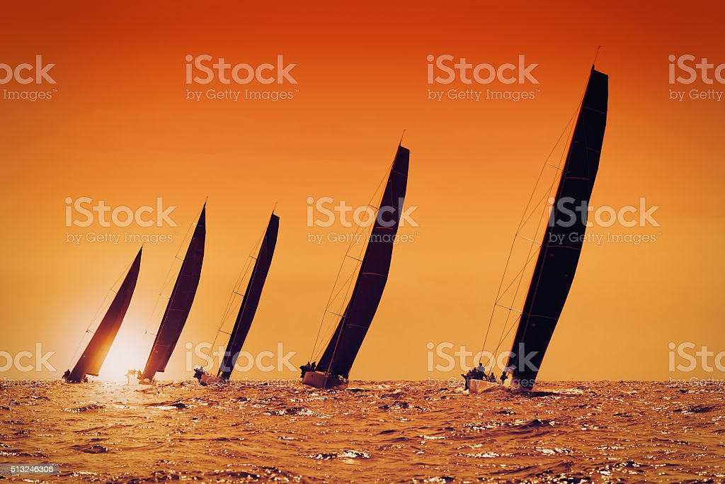 sailing yachts at sunset on the sea stock photo