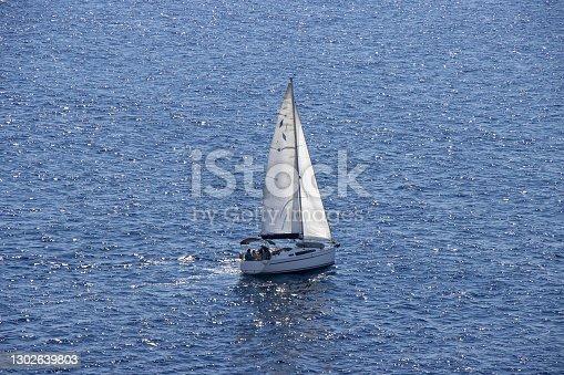 istock Sailingboat with white sails at opened sea 1302639803