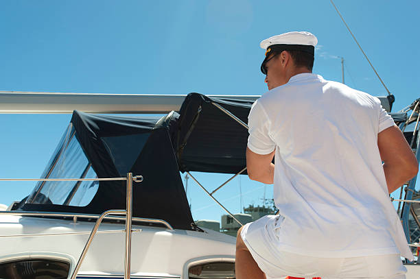 Sailor boarding a sailboat Sailor boarding a sailboat with blue sky sailor hat stock pictures, royalty-free photos & images
