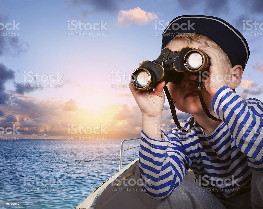 Sailor boy with binoculars in the boat stock photo
