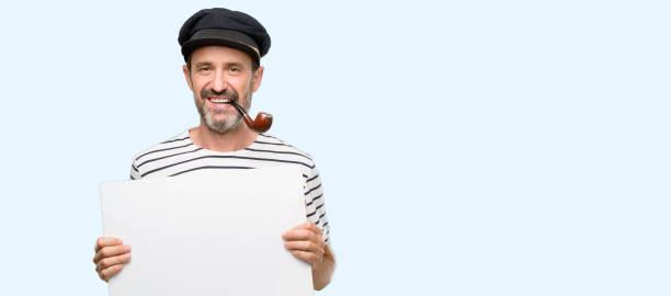 matrose kapitän mann hält leere werbebanner, gutes poster für werbung, angebot oder ankündigung, große papier plakat tabakpfeife rauchen - matrosin kostüm stock-fotos und bilder