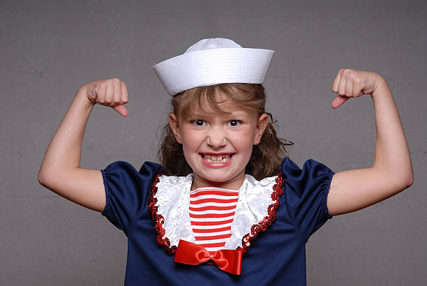 Sailor Girl Muscles A young girl in a sailor costume flexing her muscles shot with a Nikon D200 sailor hat stock pictures, royalty-free photos & images