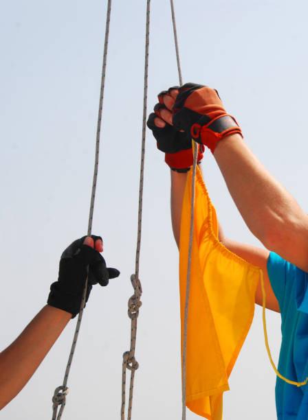 segler hängen gelbe flagge - segelhandschuhe stock-fotos und bilder