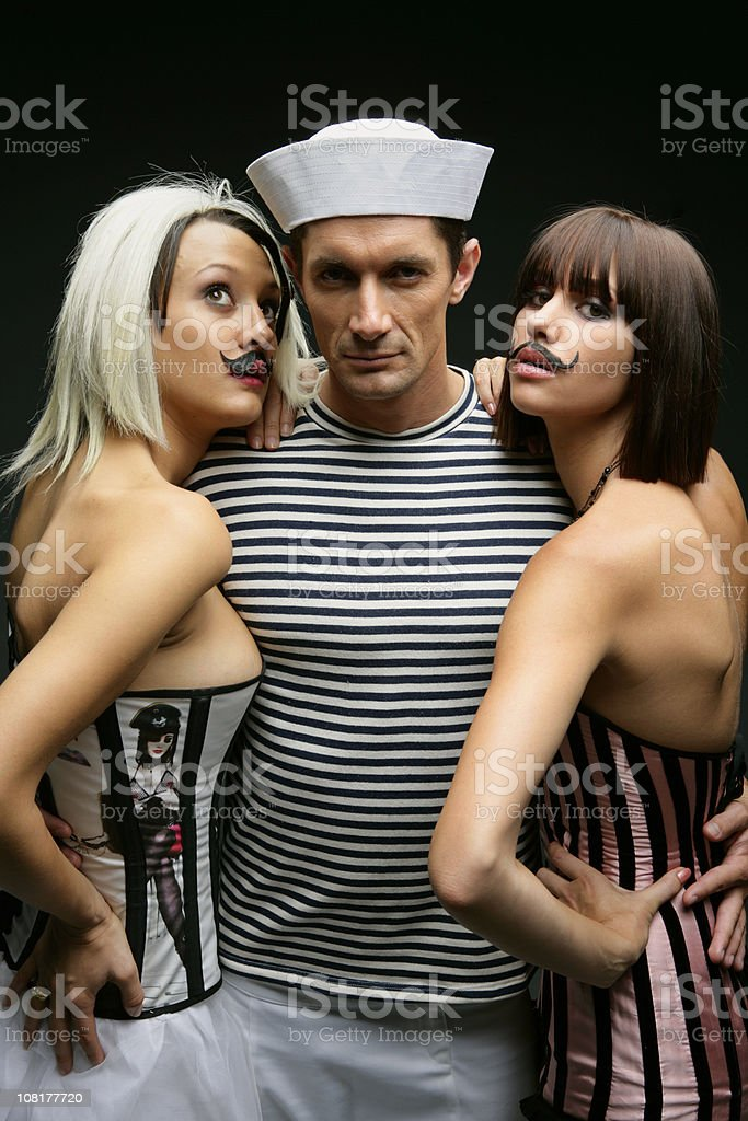 Sailor Man Embracing Two Young Women with Mustaches royalty-free stock photo