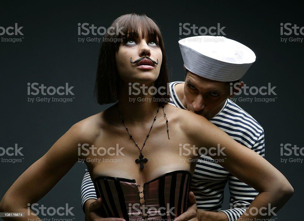 Sailor Man Kissing Young Woman Wearing Fake Mustache stock photo
