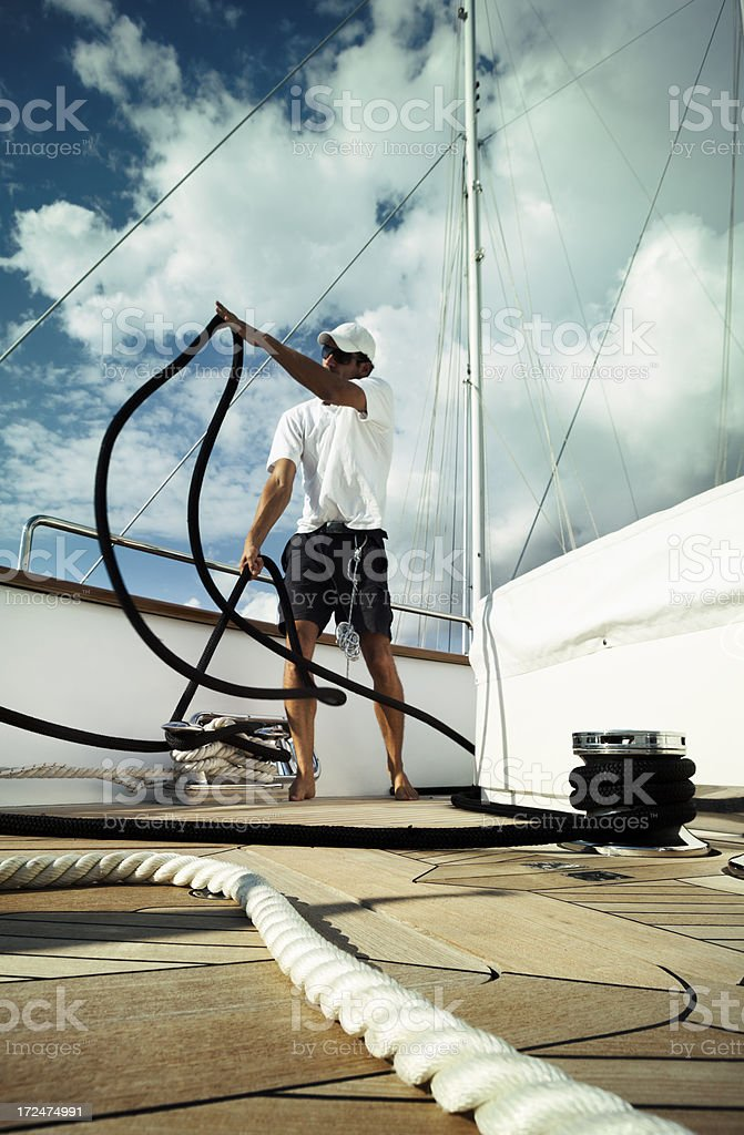 Sailor on the yacht throwing ropes. Maneuver. Sport. Summer. royalty-free stock photo