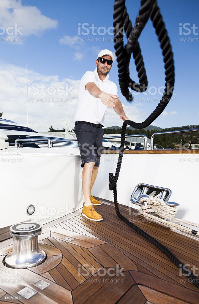 Sailor on Yacht Deck throwing the ropes forward. royalty-free stock photo