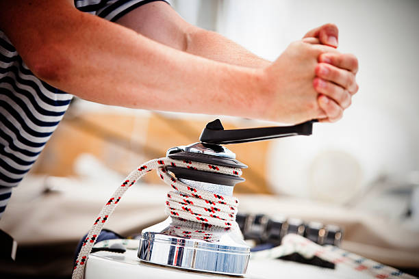 sailor winding rope of foresail with rotating handle on winch - cable winch stock photos and pictures