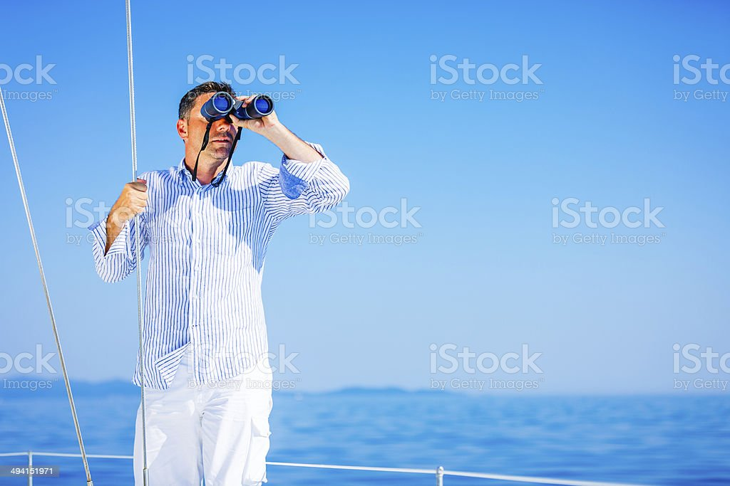 Sailor with binoculars on sailboat stock photo