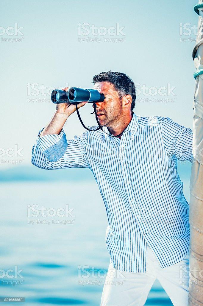Sailor with binoculars on sailboat stock photo