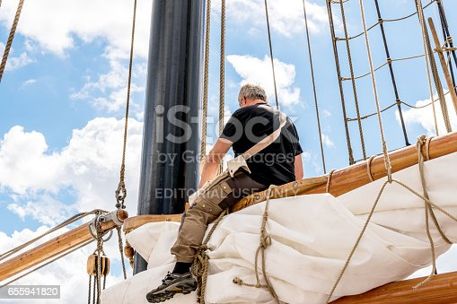 1011210354 istock photo Rostock, Germany - August 2016: Sailor working on sailing ship. 655941820