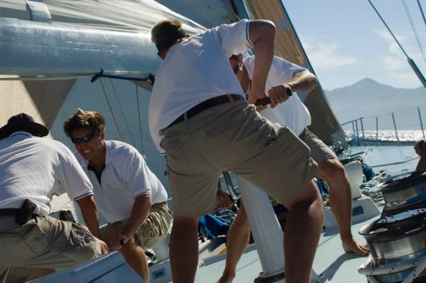 Sailors working on windlass on yacht stock photo