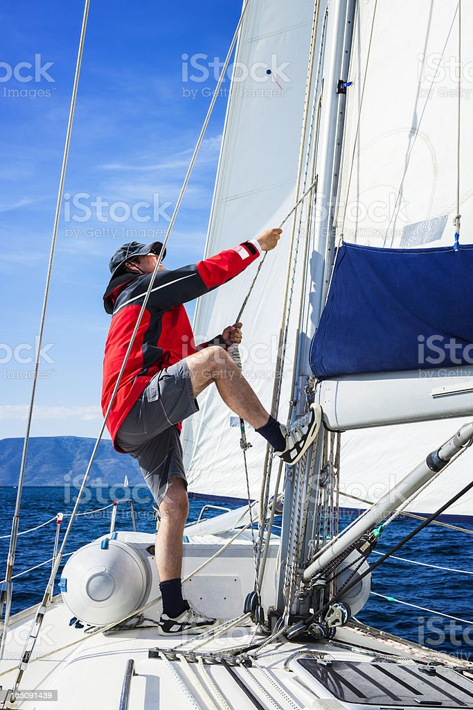 Sails up, sailor is hoisting the mainsail royalty-free stock photo