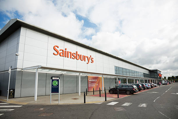 "Sainsbury's Supermarket, Glasgow ""Glasgow, UK - September 25, 2012: Cars park outside a large Sainsbury's supermarket on the outskirts of Glasgow. A number of shoppers can be seen around the main entrance.Sainsbury's is one of the largest supermarket chains in the UK."" theasis stock pictures, royalty-free photos & images"