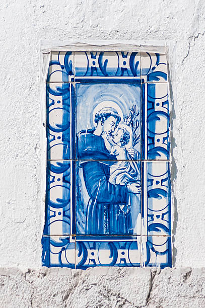 Saint Anthony of Lisbon A tile painting of Santo António ( European Portuguese) or Santo Antonio ( Brazilian Portuguese) in Lisbon, also known as St. Anthony of Padua, OFM ( Lisbon , 15 of August of 1191 - 1195 - Padua , 13 of June of 1231), of uncertain surname but baptized as Fernando, was a Doctor of the Church who lived at the turn of the centuries XII and XIII. His reputation for holiness led him to be canonized by the Catholic Church shortly after his death, distinguishing himself as a theologian , mystic , ascetic and especially as noted speaker and great miracle worker . Antonio is also considered one of the most remarkable intellectuals of Portugal's pre-university period. st. anthony of padua stock pictures, royalty-free photos & images