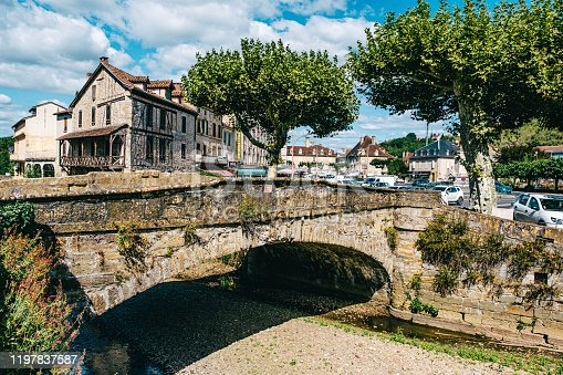 Looking along the Bave river at the junction of Quai des Recollets and Quai Jules Ferry in the village of Saint Cere in the Dordogne region of France.