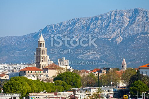 Split, Croatia - April 16 2019: Bell towers of Saint Domnius Cathedral and the Chapel of the Holy Arnir with the Mosor mountains behind.