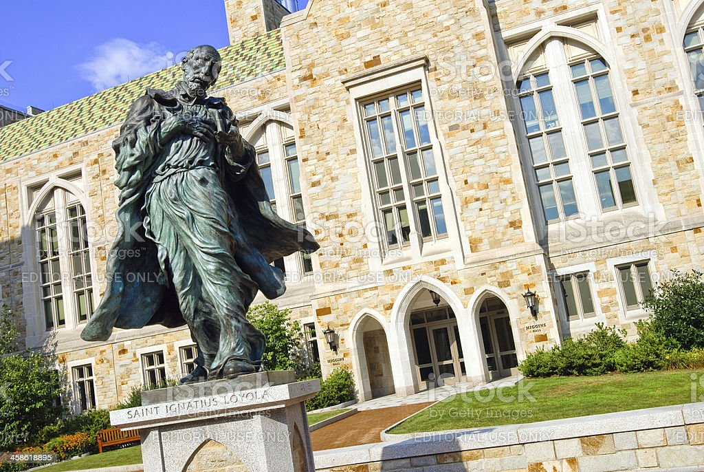 Saint Ignatius Loyola statue and Higgins Hall at Boston College stock photo