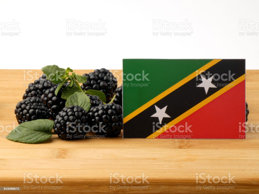 Saint Kitts and Nevis flag on a wooden panel with blackberries isolated on a white background stock photo